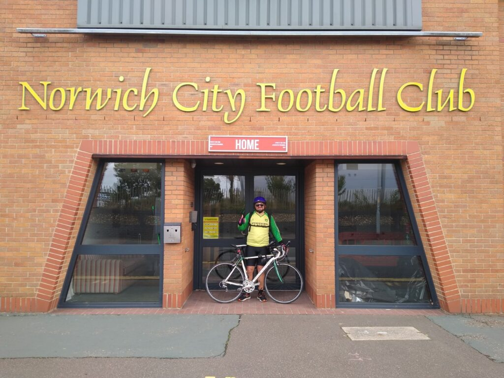 Colo standing with his bicycle outside the entrance to Norwich City Football Club.
